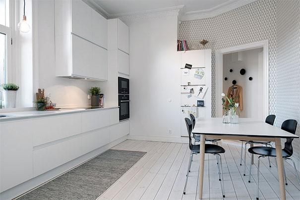 Kuchnia z nowoczesnymi meblami, rustykalną podłogą, geometryczną tapetą i klasycznymi listwami sztukateryjnymi