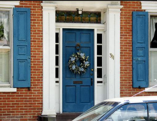 Niebieskie drzwi obudowane białymi pilastrami
