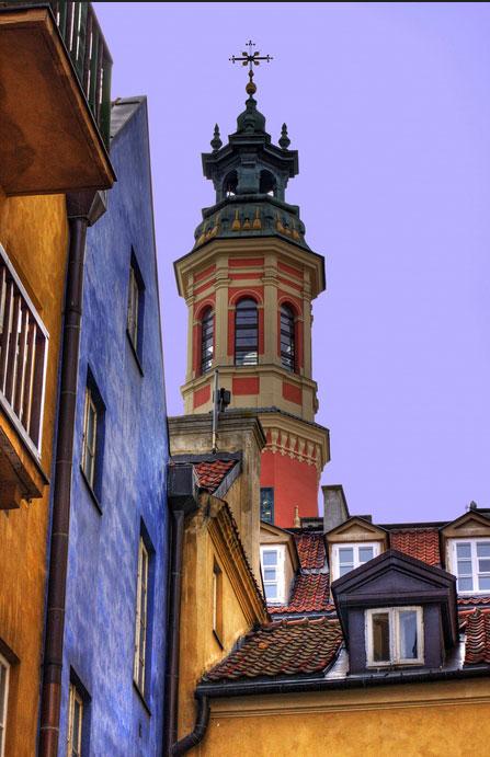 Poddasze kamienicy z widoczną wieżą kościoła