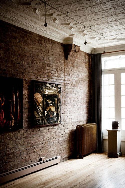 Połączenie surowej ceglanej ściany z bogato zdobionym sufitem