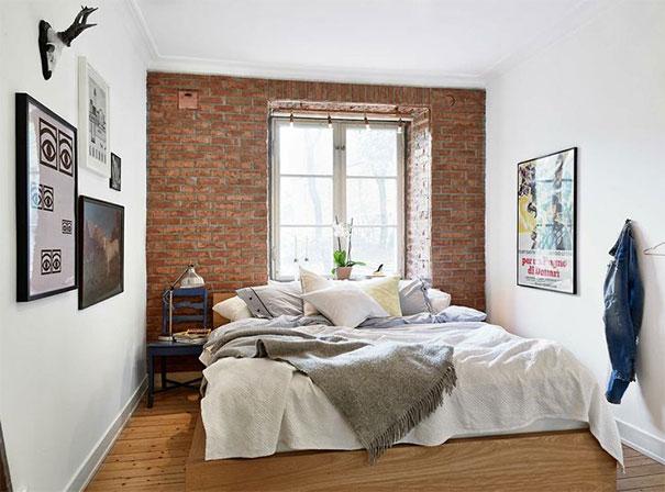 Łóżko na tle ceglanej ściany w sypialni