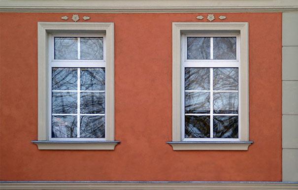 Widoczne okna z opaskami i parapetami sztukateryjnymi